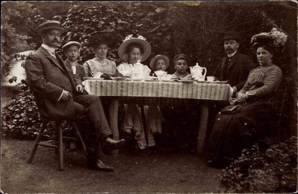 Foto Ak Familienportrait, Gedeckter Kaffeetisch, Frauen, Kinder, Männer