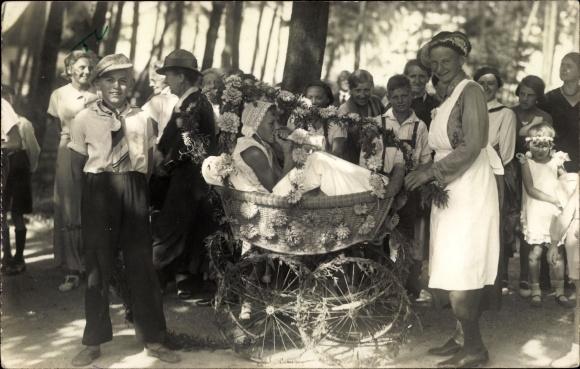 Foto Ak Kinder, Mädchen als Baby verkleidet im Kinderwagen, Blumenfest