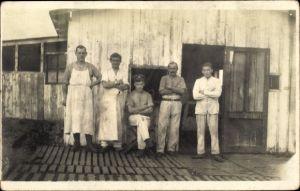 Foto Ak Maler und Schlachter in Dienstkleidung?, Gruppenportrait vor einem Holzhaus