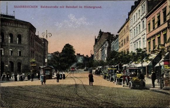 Ak Saarbrücken im Saarland, Reichsstraße, Bahnhof im Hintergrund, Autos, Straßenbahn, Passanten