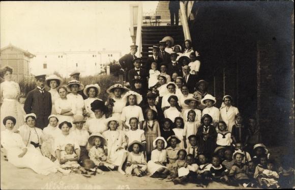 Foto Ak Männer, Frauen und Kinder vor einer Treppe am Strand