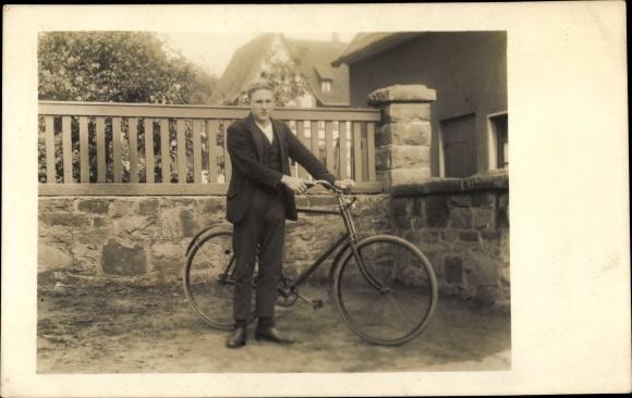 Foto Ak Junger Mann mit einem Fahrrad, Garten