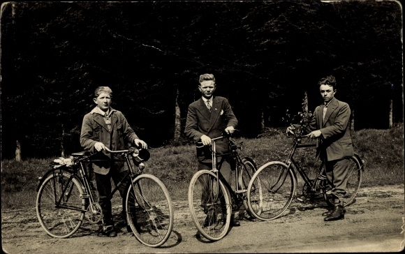 Foto Ak Drei Männer mit Fahrrädern, Hosenklammer