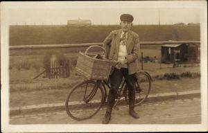 Foto Ak Radfahrer, Fahrrad, Fahrradkorb, junger Mann, Mütze