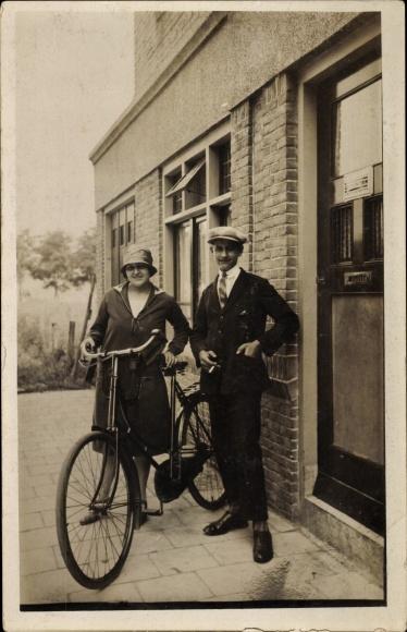 Foto Ak Paar vor einem Haus, Frau mit Fahrrad, Hut, Mantel, Mann Zigarette rauchend