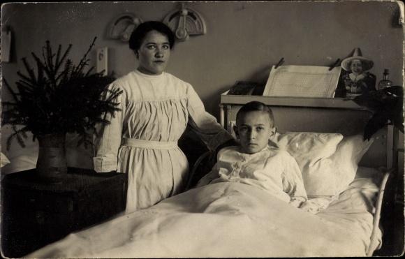 Foto Ak Krankes Kind im Bett, Krankenschwester