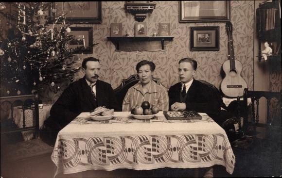Ak Frohe Weihnachten, Familie am Weihnachtstisch, Tannenbaum, Gitarre, Obst, Brettspiel