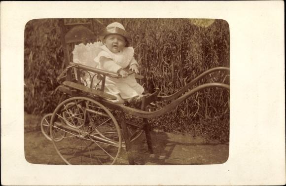 Foto Ak Kleinkind in einem Kinderwagen, Mütze