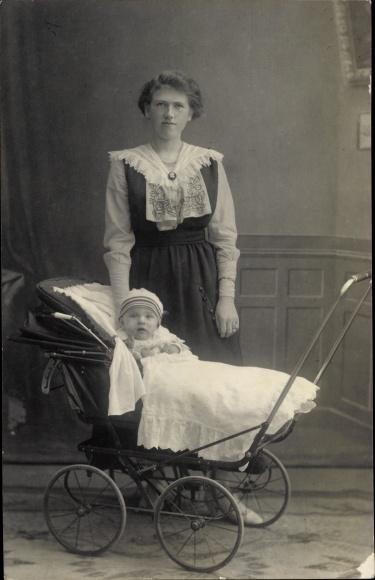 Foto Ak Kind im Kinderwagen, Frau im Kleid, Kragen, Brosche
