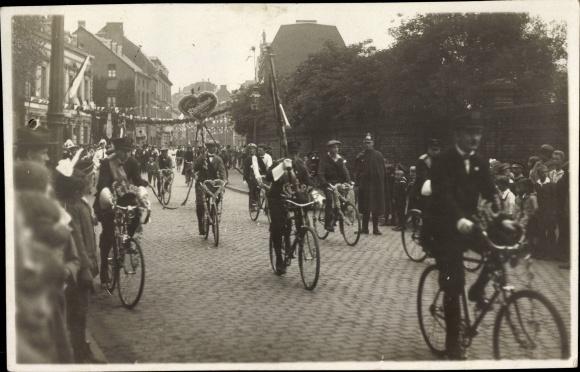 Foto Ak Rheinland?, Festumzug, Männer auf geschmückten Fahrrädern, Polizist, Zuschauer