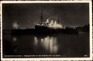 Ak Cuxhaven in Niedersachsen, Hapag Dampfer an der Amerika Pier bei Nacht
