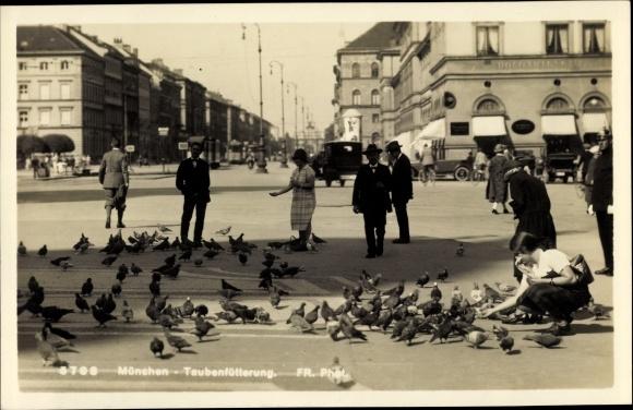 Ak München Bayern, Passanten füttern Tauben, Autos, Straßenbahnen, Geschäfte, Wohnhäuser