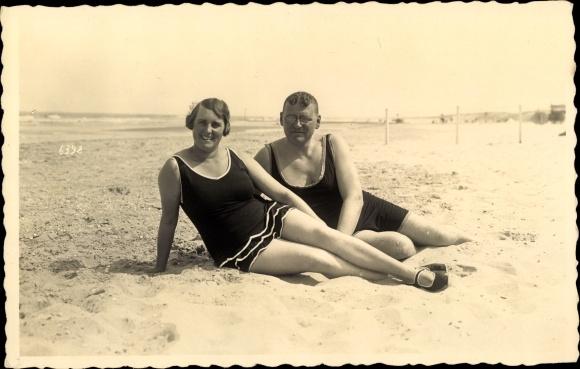 Foto Ak Mann und Frau in Badeanzügen am Strand im Sand liegend 0