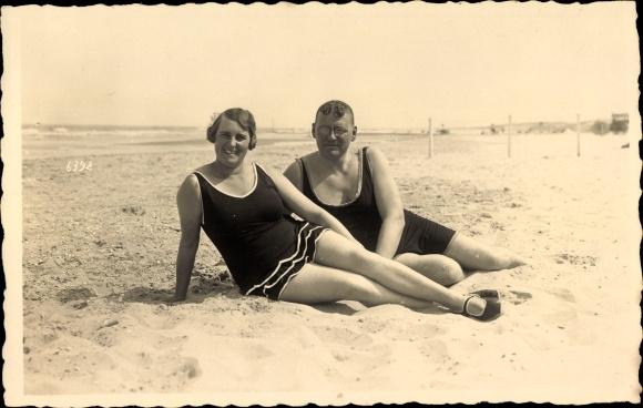 Foto Ak Mann und Frau in Badeanzügen am Strand im Sand liegend