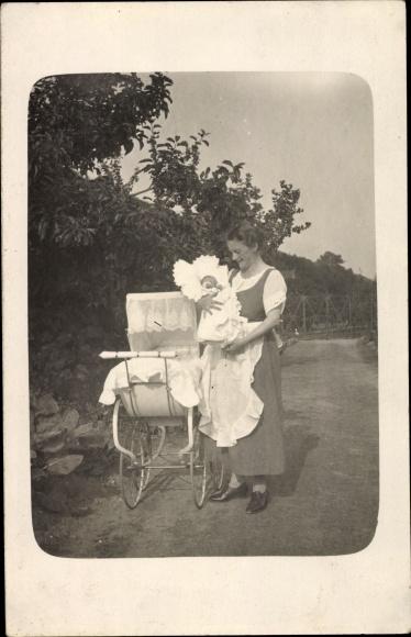 Foto Ak Frau mit Baby im Arm neben einem Kinderwagen