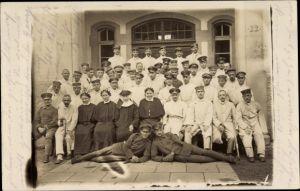 Foto Ak Deutsche Soldaten im Kriegslazarett, Gruppenportrait, Krankenschwestern