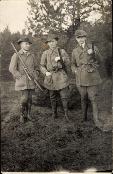Foto Ak Drei Jäger mit Gewehren auf einer Wiese, Stiefel, Portrait