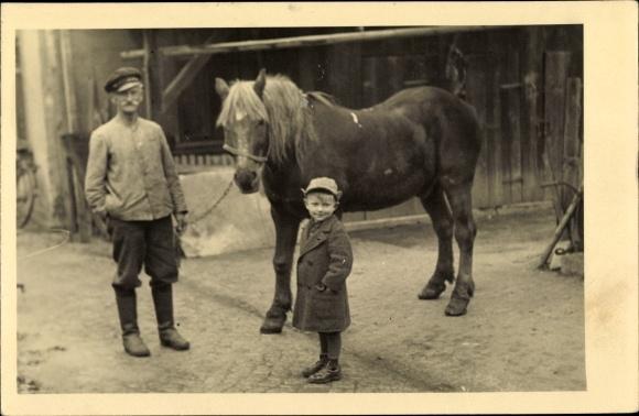 Foto Ak Mann und kleiner Junge im Mantel mit einem Pferd