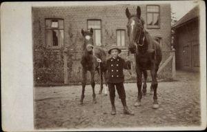 Foto Ak Junge mit zwei Pferden, Fohlen