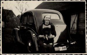 Foto Ak Estland, Junge Frau mit einem Hundewelpen vor einem Auto
