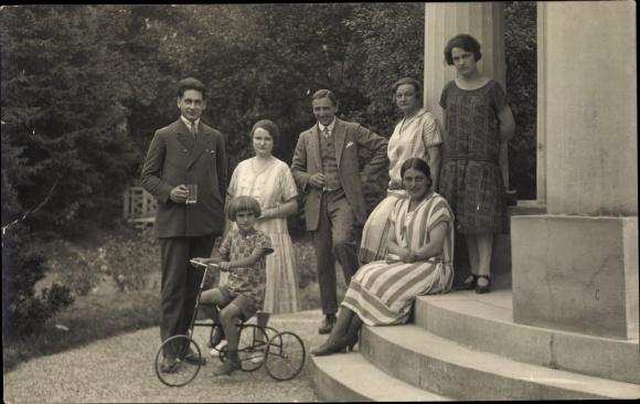 Foto Ak Kind auf einem Dreirad, Familie auf Eingangstreppe, Portal, Garten