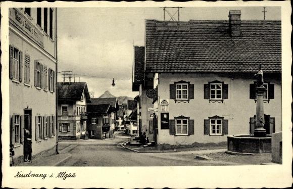Ak Nesselwang im Ostallgäu, Brunnen, Gasthaus, Straßenpartie