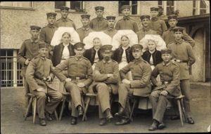 Foto Ak Deutsche Soldaten im Lazarett, Krankenschwestern, Gruppenportrait