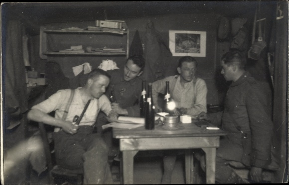Foto Ak Vier deutsche Soldaten in einem Unterstand am Tisch, Weinflaschen