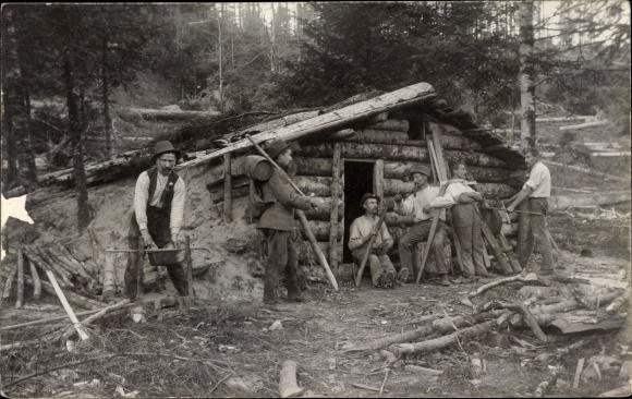 Foto Ak Männer vor einer Holzhütte im Wald
