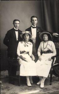 Foto Ak Zwei junge Paare, Männer in Anzügen, Junge Frauen in Hüten und Kleidern