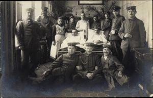 Foto Ak Deutsche Soldaten im Lazarett, Verwundete Soldaten im Krankenbett, Arzt, Krankenschwester