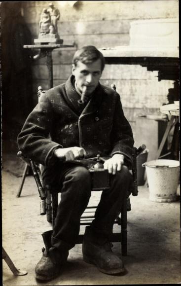 Foto Ak Junger Mann mit einer Kaffeemühle, Pfeife