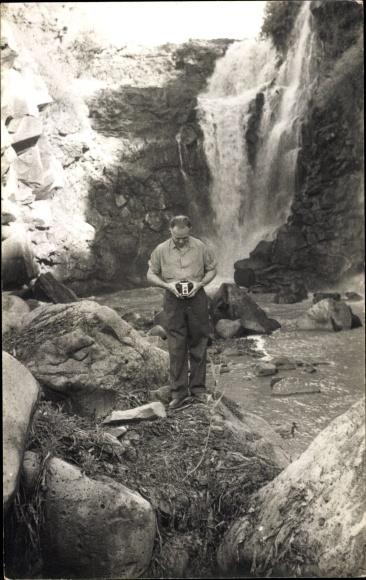 Foto Ak Mann mit Fotoapparat an einem Wasserfall