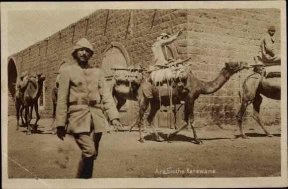 Foto Ak Arabische Karawane, Kamele mit Reitern vor einem Gebäude