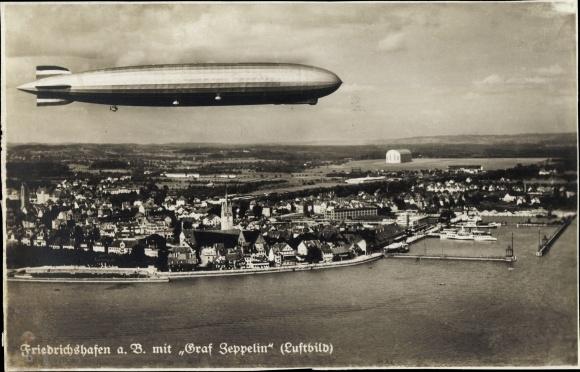 Ak Friedrichshafen am Bodensee, Luftschiff LZ 127 Graf Zeppelin über der Stadt, Fliegeraufnahme