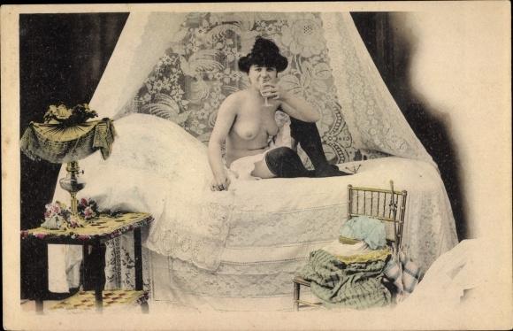 Ak Nackte Frau auf einem Bett, Busen, Strümpfe, Sektglas