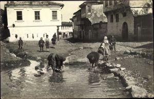 Foto Ak Mazedonien?, Wäscherinnen am Fluss, Straßenpartie