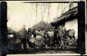 Foto Ak Deutsche Soldaten in einem Dorf, Gruppenbild mit Einheimischen