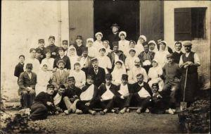 Foto Ak Gruppenbild mit Krankenschwester und verwundeten Soldaten