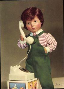 Ak Käthe Kruse Puppen, Junge in Latzhose mit einem Telefon