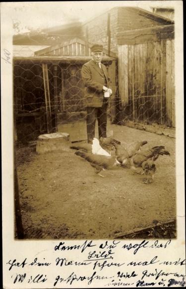 Foto Ak Hühner, Mann im Stall beim Füttern