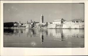 Foto Ak Kroatien, Blick zum Ort, Kirchturm, Wasserspiegelung
