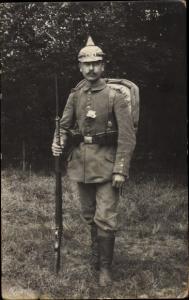 Foto Ak Deutscher Soldat in Felduniform, Munitionsgürtel, Gewehr