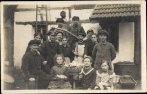 Foto Ak Männer, Frauen, Kinder vor einem Haus, Schlachtbank, Innereien, Wurst