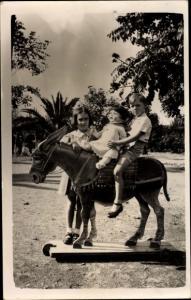 Foto Ak Junge mit Puppe auf einem Spielzeugpferd, Mädchen, Schaukelpferd