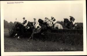 Foto Ak Pferderennbahn Hoppegarten, Rennpferde, Jockeys, Sprung über Hindernis