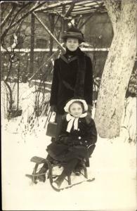 Foto Ak Frau mit Hut und Wintermantel, Mädchen auf einem Schlitten, Handtasche