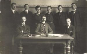 Foto Ak Gruppenfoto von Männern in Anzügen und Frauen, Schreibtisch, Stempel