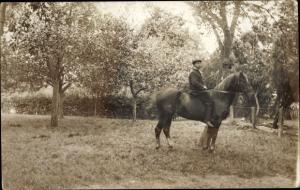 Foto Ak Mann in Reitkleidung und mit Mütze auf einem Pferd