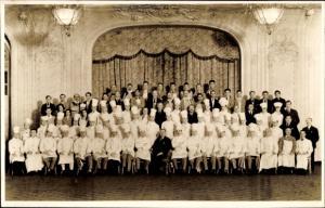 Foto Ak Gruppenfoto von Köchen und Kellnern vor einer Bühne, Restaurant